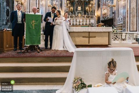 Foto de boda en la iglesia de Puglia de una niña de las flores sentada y leyendo durante la ceremonia