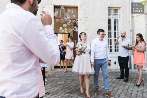 Agen, France outdoor wedding photo of the bride and groom exiting under bubbles