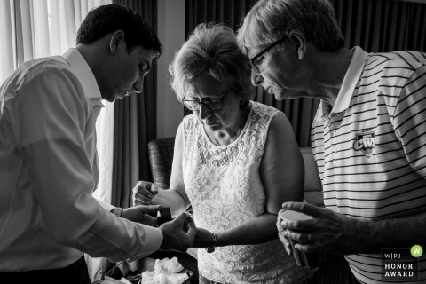 Pennsylvania wedding photo from the Hotel during prep as the Groom shows the wedding band to his parents