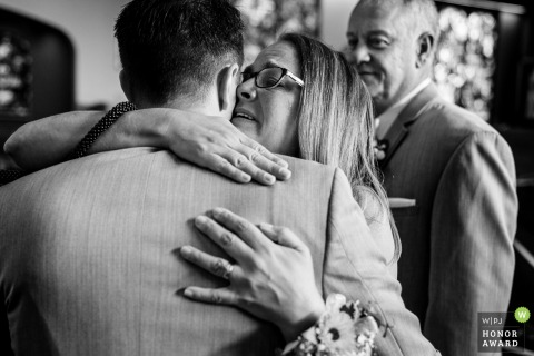 Pennsylvania wedding photo of Grooms mom hugging him after walking down the aisle and tears up as his father looks on