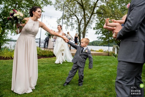 Wisconsin wedding photo from the outdoor Reception at the couple's home of the Bridesmaid's son looking for attention