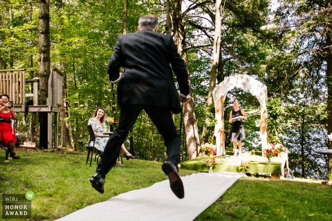 Verona, On outdoor wedding ceremony photo from the bride and groom's home of the groom making a grand entrance down the aisle