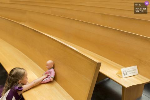 Oakland California iglesia boda imagen de una niña jugando con una muñeca en los bancos