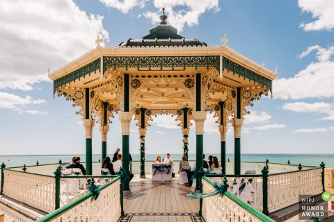 Outdoor wedding photo from Brighton Bandstand, Brighton, England	created as a Couple signs the register at their small outdoor wedding with views of the sea beyond