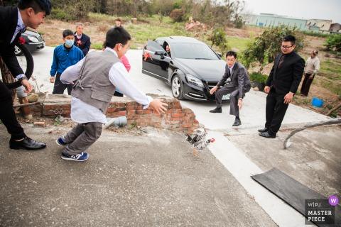 De bruidegom uit Taichung Taiwan en zijn gezin jagen op de loden kip van de bruid bij het huis van de bruid