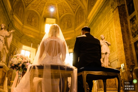 San Pietro in Montorio Church, Rome, Italy wedding image showing the sunlight enters directly from the window during the ceremony on the praying couple