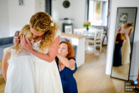 Een bruid uit Hauts-de-France die haar dochter geruststelt terwijl haar moeder haar trouwjurk sluit