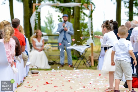 Nord outdoor wedding photo of children playing with the rose petals while the groom makes his speech