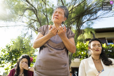 De moeder van een bruidegom uit de Auvergne-Rhône-Alpes heeft een sterk emotioneel moment en rondt een gebed af met de zussen van de bruidegom aan de zijde