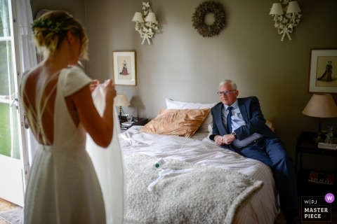 Hauts-de-France father of the bride looking at his daughter adjusting her veil in this hotel wedding image