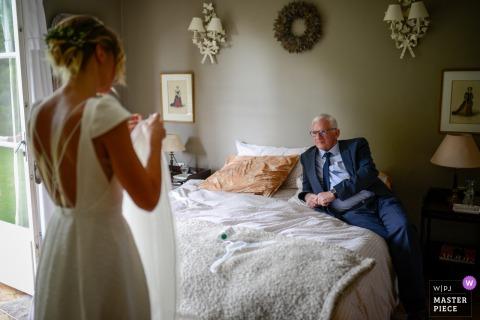 De vader van de bruid uit Hauts-de-France kijkt naar zijn dochter terwijl hij haar sluier aanpast in dit hotelhuwelijk