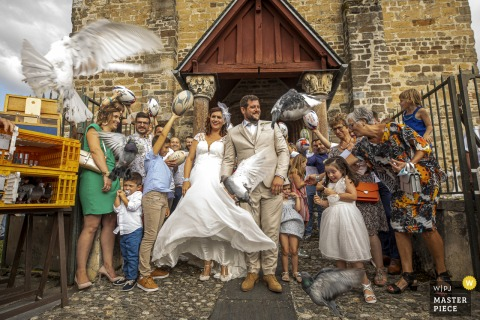 Occitanie	wedding image from Behind church of the birds being released for the bride and groom