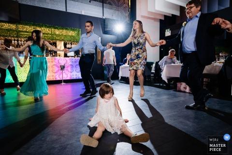 Afbeelding van een klein meisje dat op de vloer zit totdat anderen dansen in het Koriata Restaurant, de trouwlocatie van Sofia, Bulgarije