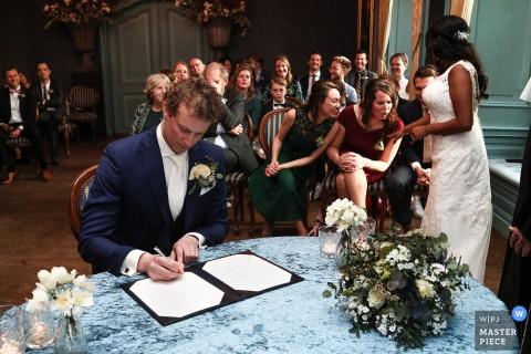 La mariée montre son alliance à ses meilleurs amis, tandis que son nouveau mari signe le certificat de mariage à Kasteel Wijenburg Echteld