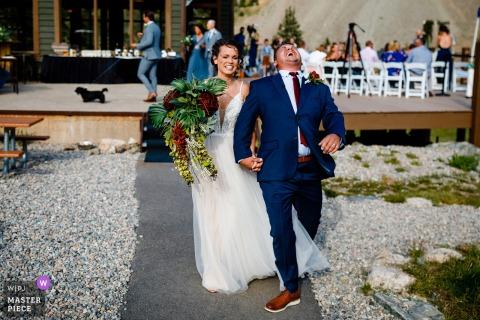 De bruidegom lacht terwijl hij met zijn nieuwe vrouw het eiland afloopt na hun buitenceremonie in Arapahoe Basin, CO