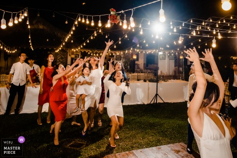 Huwelijksfotografie in Vietnam bij de receptie van de bruid die het boeket naar haar alleenstaande gasten gooit