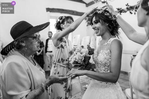 Terwijl de bruidsmeisjes confetti uit haar haar halen, toont de bruid haar trouwring aan haar grootmoeder op Château de la Rive, Cruet, Savoie, Frankrijk