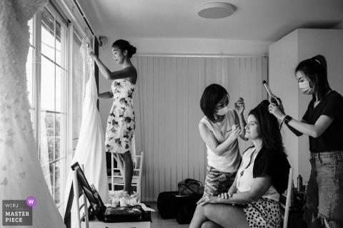 Even tijdens de bruidsvoorbereiding hing de bruid haar bruidsjurk op, terwijl de MUA's de make-up aanbrachten op de beste vriendin van de bruid in Sai Kung, Hong Kong (huis van de bruid en bruidegom)