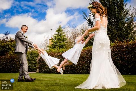 Trouwfoto van de bruid en bruidegom die Mama en Dada zijn en hun twee kleine meisjes ronddraaien tijdens de receptie in Glenview Gardens, Cork, Ierland