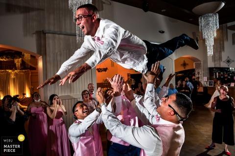 Afbeelding van de trouwlocatie van de bruidegom die in de lucht wordt gegooid door bruidsjonkers in het Bella Sera Event Center in Brighton, CO