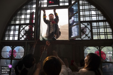 De Shaanxi-bruidegom opent het raam in deze afbeelding van de Chinese gatecrashing