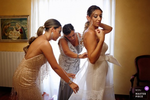 Wedding image from the House of the Bride in Siderno, Reggio Calabria of the Getting ready Bride with The sisters while helping the bride