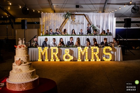 Cog Hill Country Club wedding photo of the bridal party seated for the meal under a Mr & Mrs lighted sign by the cake