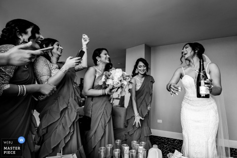 Image of the bride opening a champagne bottle at the Hilton Chicago/Oak Brook Hills Resort & Conference Center