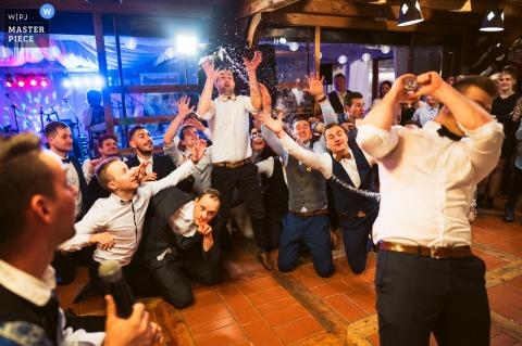 Une image de réception de mariage en Slovénie du marié jetant une eau au lieu d'une jarretière