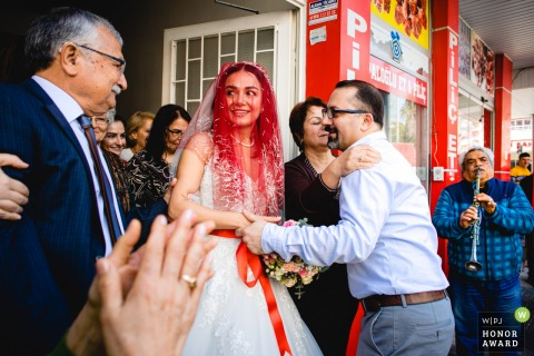 Mersin Silifke Turkey wedding photo of the bride surrounded by guests and live musicians - Bride and her father's emotional goodbye moment