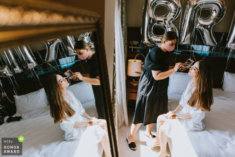 Mersin Hilton Hotel, Turkey wedding photo of the bride having makeup applied by a mirror