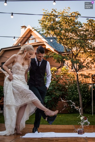 Sofia, Bulgaria, private home and garden wedding reception image of the bride and groom kicking together