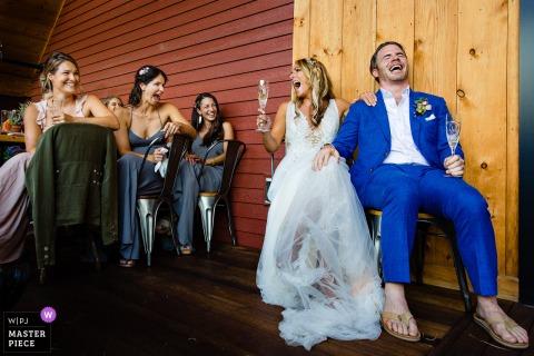Een bruid en bruidegom uit Scarborough, Maine lachen met vrienden tijdens een huwelijksreceptie