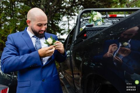 Photo de mariage du parc national d'Acadia d'un homme épinglant sa fleur à son manteau de costume à l'extérieur