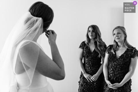 Blue Hill, Maine Bruidsmeisjes kijken toe terwijl de bruid voor de bruiloft haar sieraden aantrekt