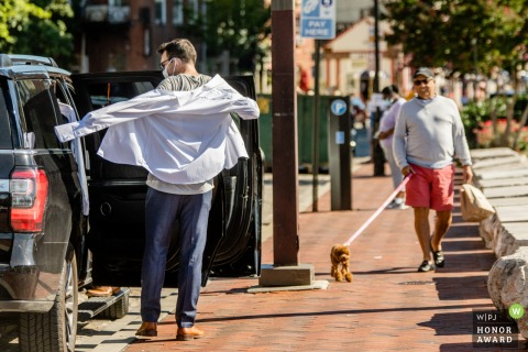 Baltimore Inner Harbor Getting Ready wedding photo of the groom dressing outside of a car