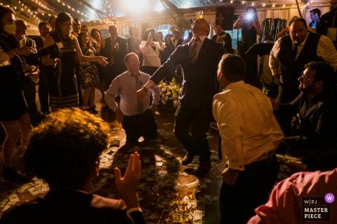 Bruiloftsgasten voeren een Griekse huwelijkstraditie uit tijdens de huwelijksreceptie in een privéwoning in Boiling Springs, PA