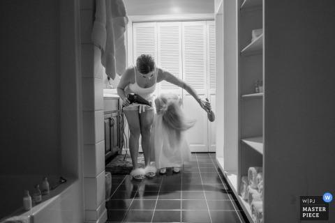 De bruid helpt een jong meisje terwijl ze zich klaarmaakt voor de bruiloft in Allenberry Resort, PA, Holy Trinity Greek Orthodox Church, met een thuisreceptie