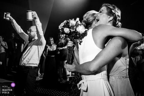 Een gelukkige Braziliaanse peetvader viert het wanneer hij ziet dat zijn vriendin het boeket neemt op de huwelijksreceptie