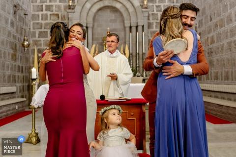 Tijdens de huwelijksceremonie van de Gramado Moederkerk knuffelen de bruid en bruidegom de bruidsmeisjes en worden kinderen jaloers