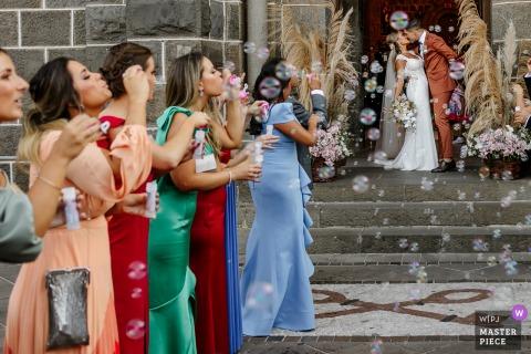 Trouwfoto van de bruid en bruidegom die kussen met zeepbellen in de Gramado-moederkerk
