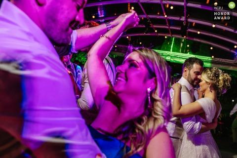 Sítio da Figueira, Porto Alegre, Brasil wedding photo of the couple and guests on the dance floor under purple dj lights