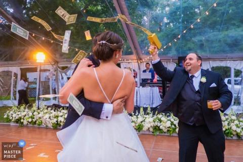 Il testimone spara banconote da un dollaro durante il primo ballo della coppia di sposini in un matrimonio nel cortile di una casa privata a Boiling Springs, Pennsylvania