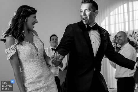 Een bruid en bruidegom lopen de huwelijksreceptie binnen in de evenementenlocatie Belle Mer