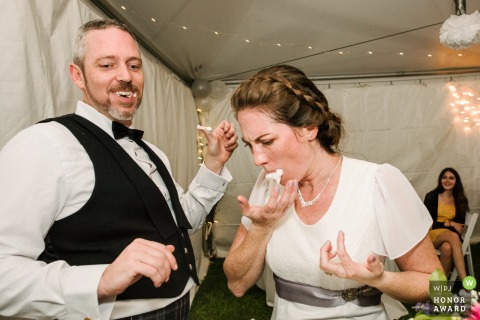 An Ottawa tented wedding reception image of the bride and groom eating cake
