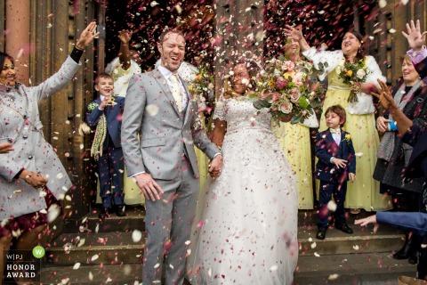Photo de reportage de mariage au Royaume-Uni de l'église St Mary the Virgin, Cambridge montrant quelques confettis folie