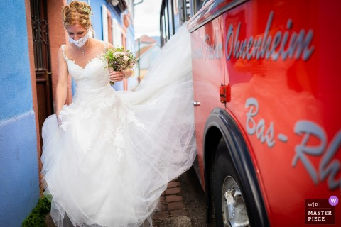Wedding photography in Bassemberg - Alsace of the bride On the way to the town hall with a red bus