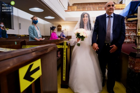 UK wedding reportage photography from a London Synagogue of the Bride walking down the aisle during a COVID19 wedding