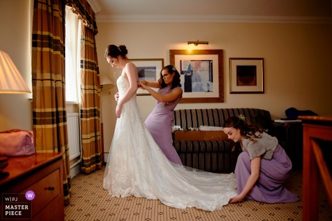 Hampshire wedding photo of an England bride Getting dressed in her hotel room with some help
