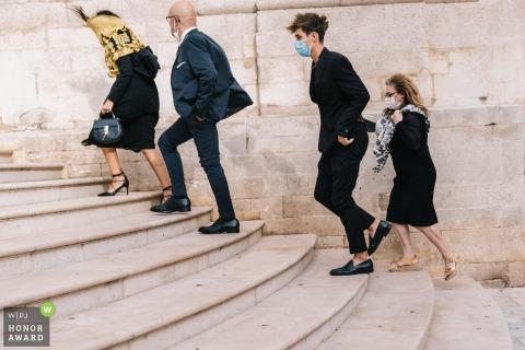 Fotografía de la boda de Puglia que muestra el fuerte viento que sopla a los invitados mientras suben los escalones